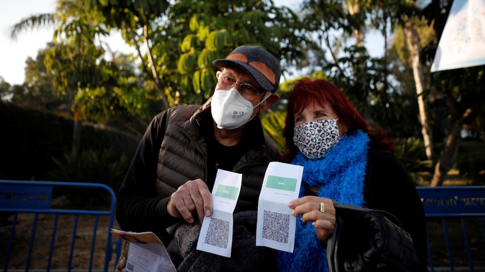 Un homme et une femme exhibent leur passeport vaccinal.