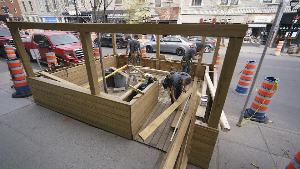 Des ouvriers installent une terrasse près d'un restaurant de la rue Mont-Royal.