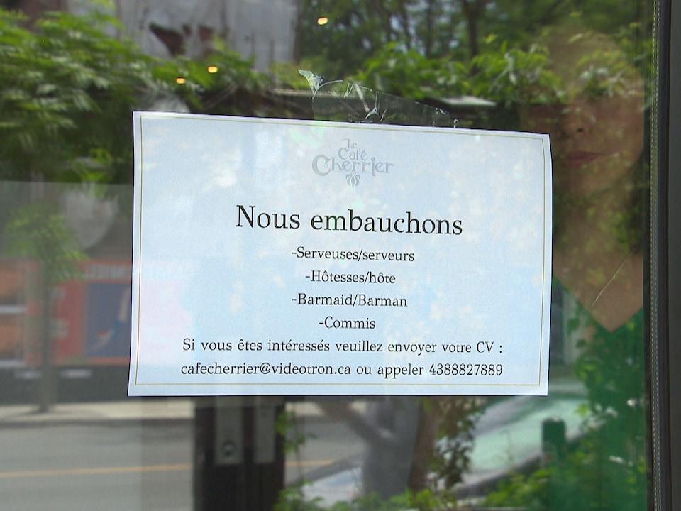 Une femme se tient derrière une fenêtre dans laquelle une feuille affiche « Nous embauchons ».