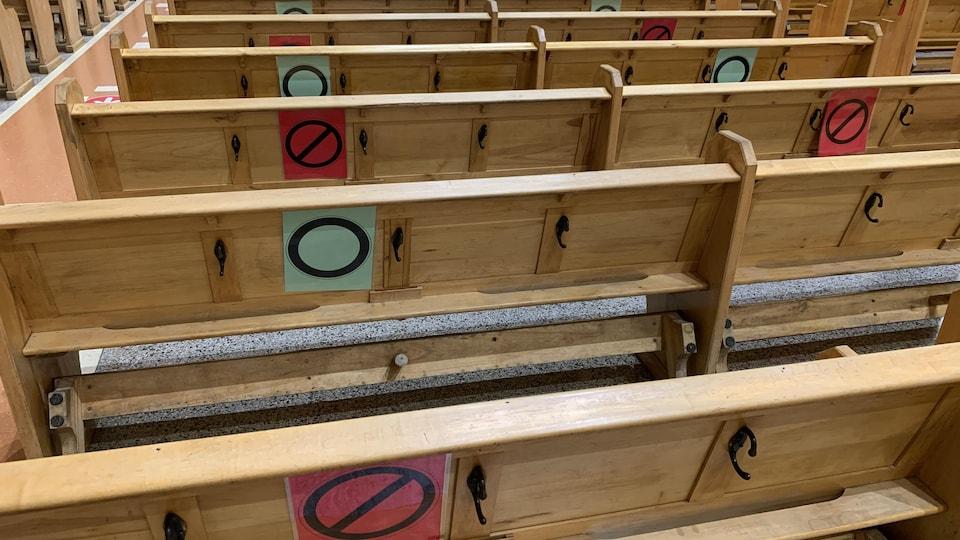 Sur des bancs d'église ont été collés des ronds verts et rouges afin de respecter les règles de distanciation.