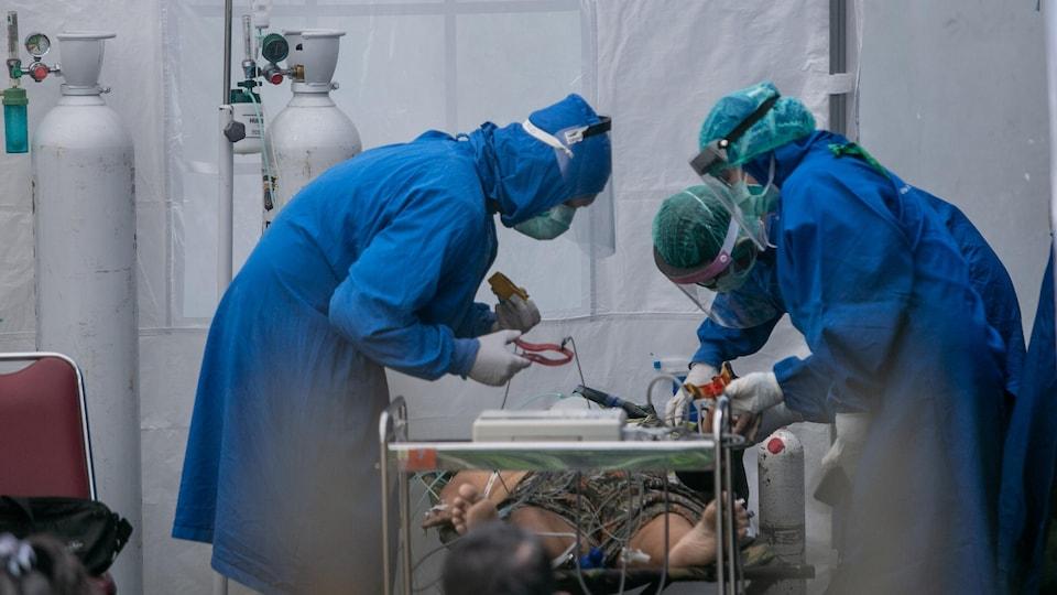 Trois soignants en combinaison bleue penchés au-dessus d'un patient alité.