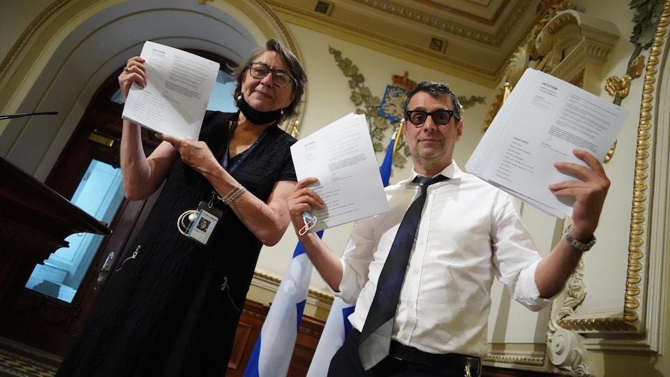 Claire Samson et Éric Duhaime tiennent des copies de la pétition à l'Assemblée nationale.